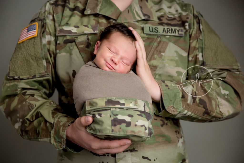 Army soldier holding smiling newborn baby