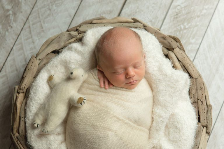 newborn baby in a bowl with tiny teddy bear