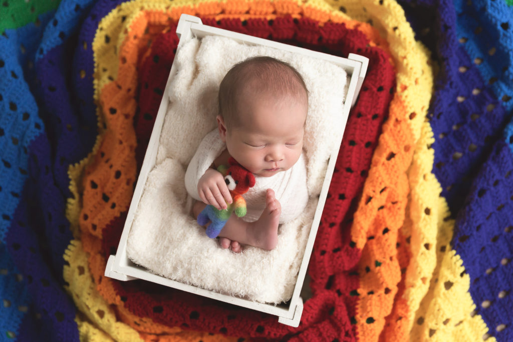 newborn baby surrounded by rainbow blanket