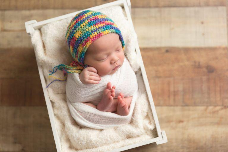 sleeping newborn with rainbow bonnet