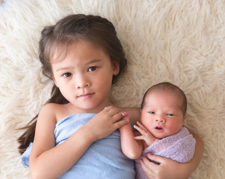 5 year old girl holding baby sister