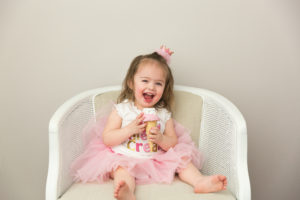 little girl in a crown sitting with an ice cream cone