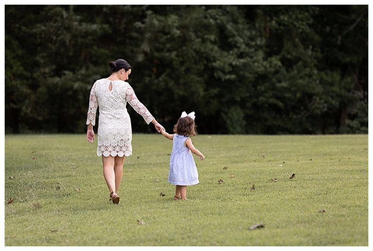 mom and daughter holding hands while walking