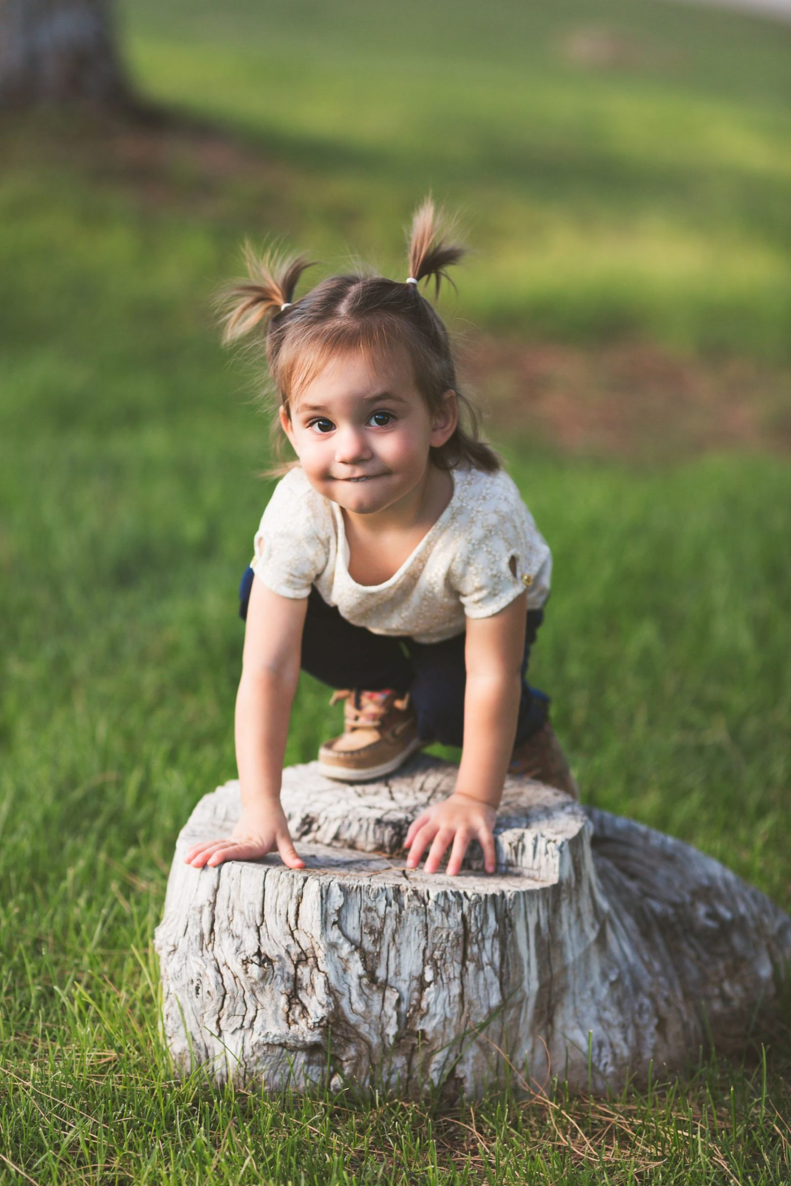 toddler girl climbing onto a tree stump