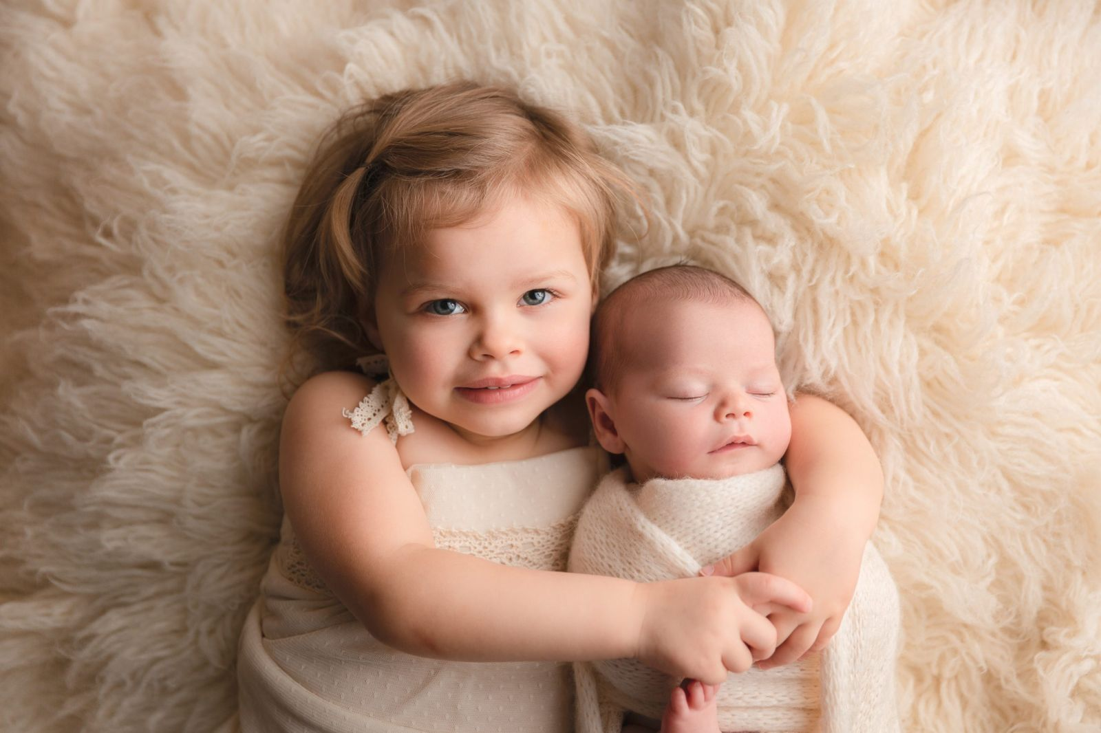 adorable 2 year old holding sleeping newborn sister